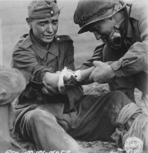 Amerykański medyk opatruje rannego nastoletniego niemieckiego żołnierza, wrzesień 1944 r.