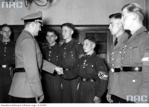 Przywódca młodzieży Rzeszy Artur Axmann (z lewej) wręcza kilku członkom Hitlerjugend Wojenny Krzyż Zasługi z Mieczami, zaś szesnastoletniemu Nikolausowi Willms (trzeci z prawej) Krzyż Żelazny II klasy, październik 1942 r